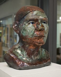 Ceramic sculpture of a bust of a head and shoulders, colored copper and green, sitting on a pedestal in front of an interior glass wall.