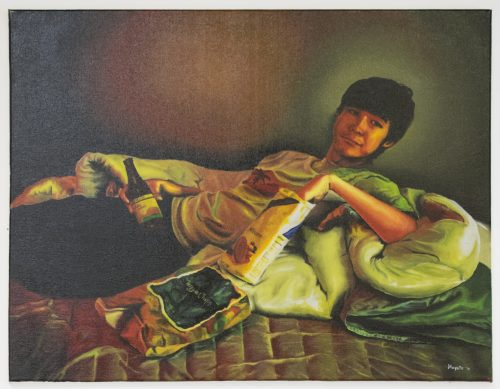 Oil painting of a young man reclining on blankets on a bed. He looks is looking towards the viewer, holding a bottled drink in one hand, while the other hand is reaching into a bag of cookies.