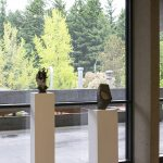Installation view of a gallery with four pedestals in a row with small ceramic sculptures placed atop each one. Behind the pedestals are floor to ceiling windows that show an outdoor walkway and green trees beyond.