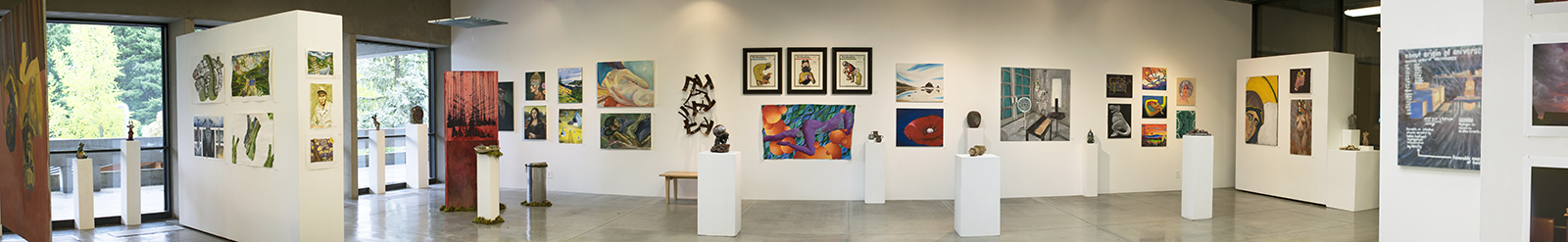 Panorama installation view of art gallery with many artworks on the far wall in the background, on additional walls to the left and rights, and of several pedestals in the middle.