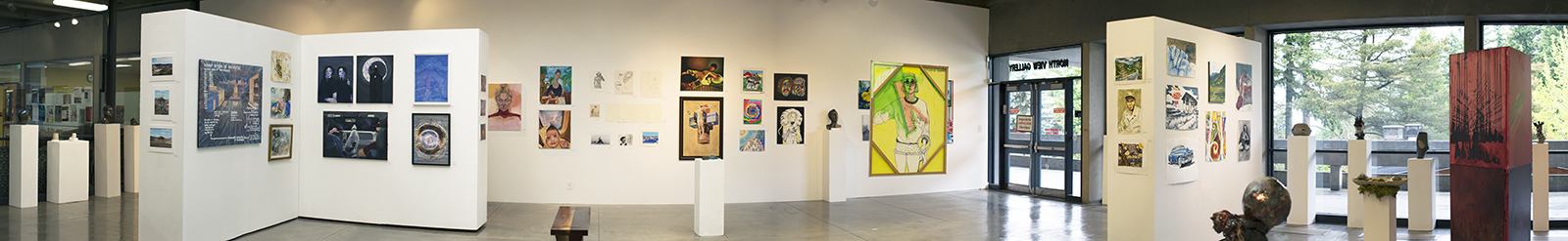Panorama installation view of gallery with several artworks on the far wall in the background, on walls on the left and right, and on pedestals throughout the room. To the left is a freestanding artwork with windows behind it.