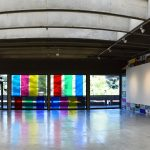 Panorama view of art gallery. On the left wall are six multicolored large abstract paintings; on the right wall are smaller multicolored abstract paintings that form a large rectangle. At center is a wall of glass windows that look out to greenery, with seven large bands of colored vinyl installed vertically across the glass.