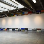 Gallery wall has an installation of 98 small paintings on paper, each measuring 11 by 30 inches. The paintings are directly adjacent to one another so as to form a rectangle at the perimeter of the wall; they form a large rectangle that touches the edges of the wall at the ceiling, the floor, and to the left and right. The center of the wall is empty except for the circular shapes created by the lighting for the artwork. The paintings are multicolored and abstract.