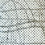 Detail view of larger wall installation. Abstract painting based on a grid, showing black dots on a grid of pencil