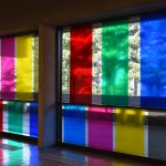 Artwork of vinyl rectangular colored decals on two glass walls. Colors include blue, red, green and yellow and are arranged as verticals. The trees and walkway are seen behind the glass.