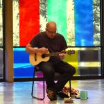 View of performance for the exhibition. A man is sitting on a chair playing a small guitar. On the floor beside him are objects. . Behind him is a wall of glass with large bands of blue, red, yellow and green vinyl.