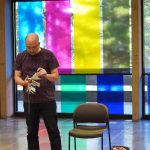 View of performance for the exhibition. A man stands to the left of an empty chair, a guitar and other objects are on the floor beside him. He is holding a large metal ring with painted cards on it and reading from the cards. Behind him is a wall of glass with large bands of blue, magenta, yellow and green vinyl.