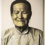 A painting of an older Asian woman in traditional clothing, with her hair pulled away from her face. The portrait is in sepia tones, highly photorealistic, and depicts just her head and shoulders, with her face looking directly at the viewer.
