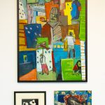 Three artworks hang on a wall. On top is a large multicolored, vertical, abstract painting depicting people in the street. On the bottom left is a small black and white print of three seated figures; on the bottom right a square painting of a woman sleeping in a bed with a child on either side of her. The painting is predominantly blue.