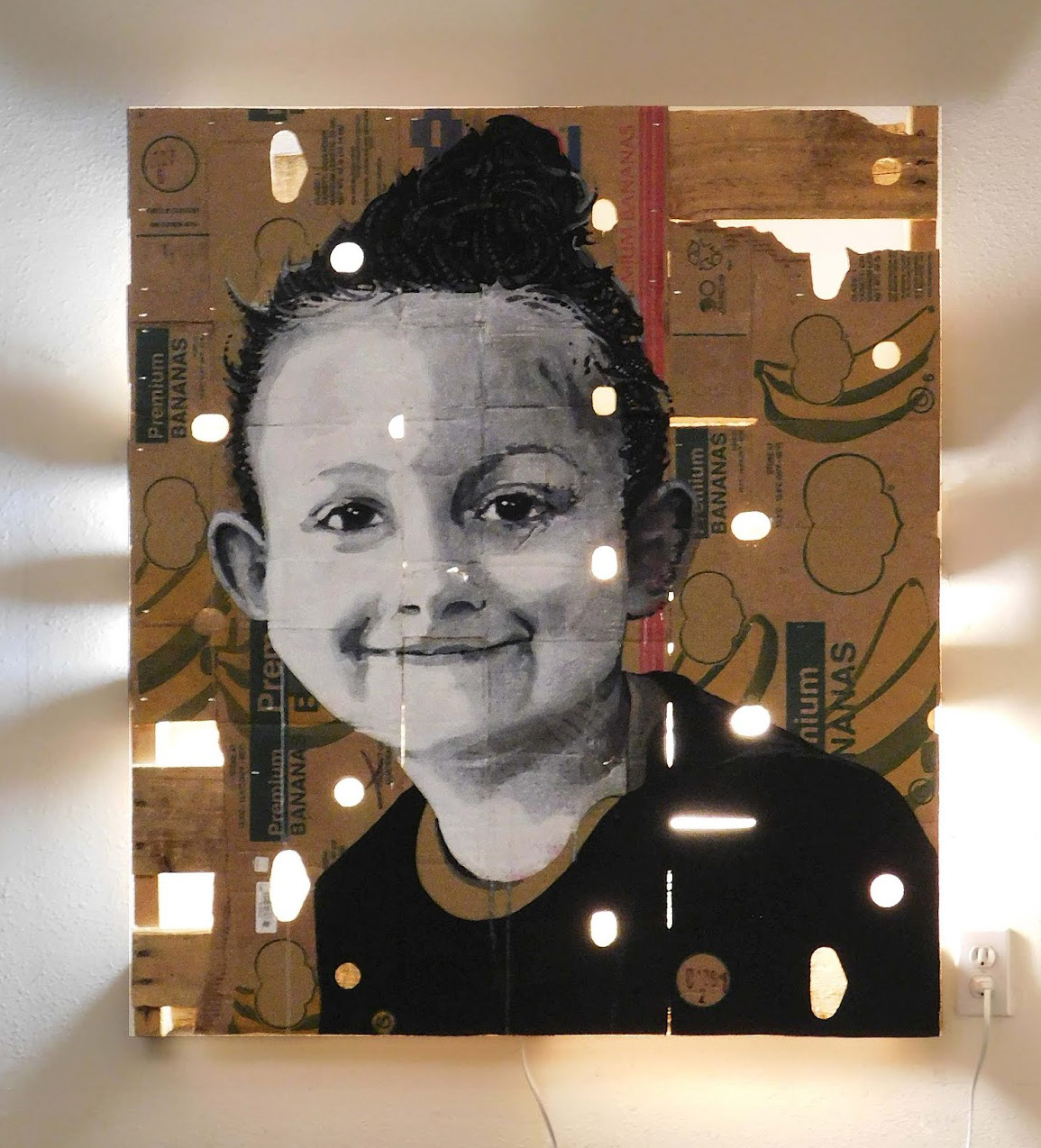 portrait of a child on a cardboard box with light shining through it.