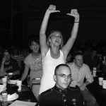 Horizontal black and white photograph of a crowd of people sitting at tables with white paper cups and other objects on the tables. They are looking towards the right side of the photo. A young man in a forman marine uniform sits in the foreground; a young woman in a white shirt stands behind him with her hand raised above her head and cheers. Behind and to her left is another woman who stands and shouts. The background is dark.
