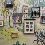 Several small scale framed photos are hung on a wallpapered wall. The photos faded and appear to be from a personal family album. The wallpaper is multicolored and depicts a pastoral scene with horses and a house on the right and grass and trees and a lake on the right.