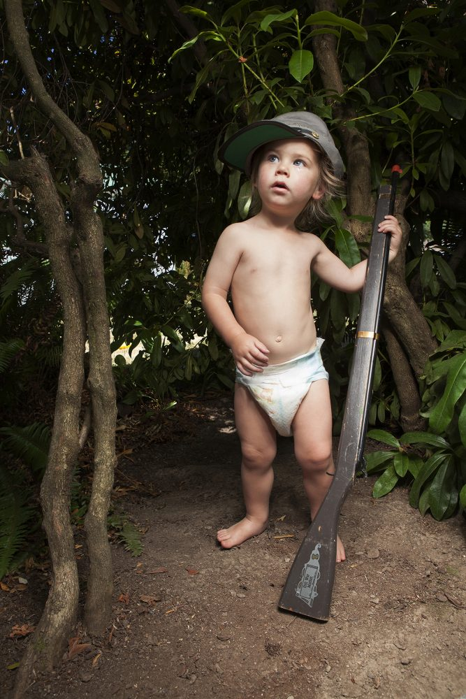 Vertical color photograph of a small boy, wearing only a diaper and a confederate army style hat, and holding a wooden replica of a civil war musket. He gazes up and to the left. He is standing on brown dirt and is surrounded by shrubs in the background. At the left of the photo are two slender tree trunks.