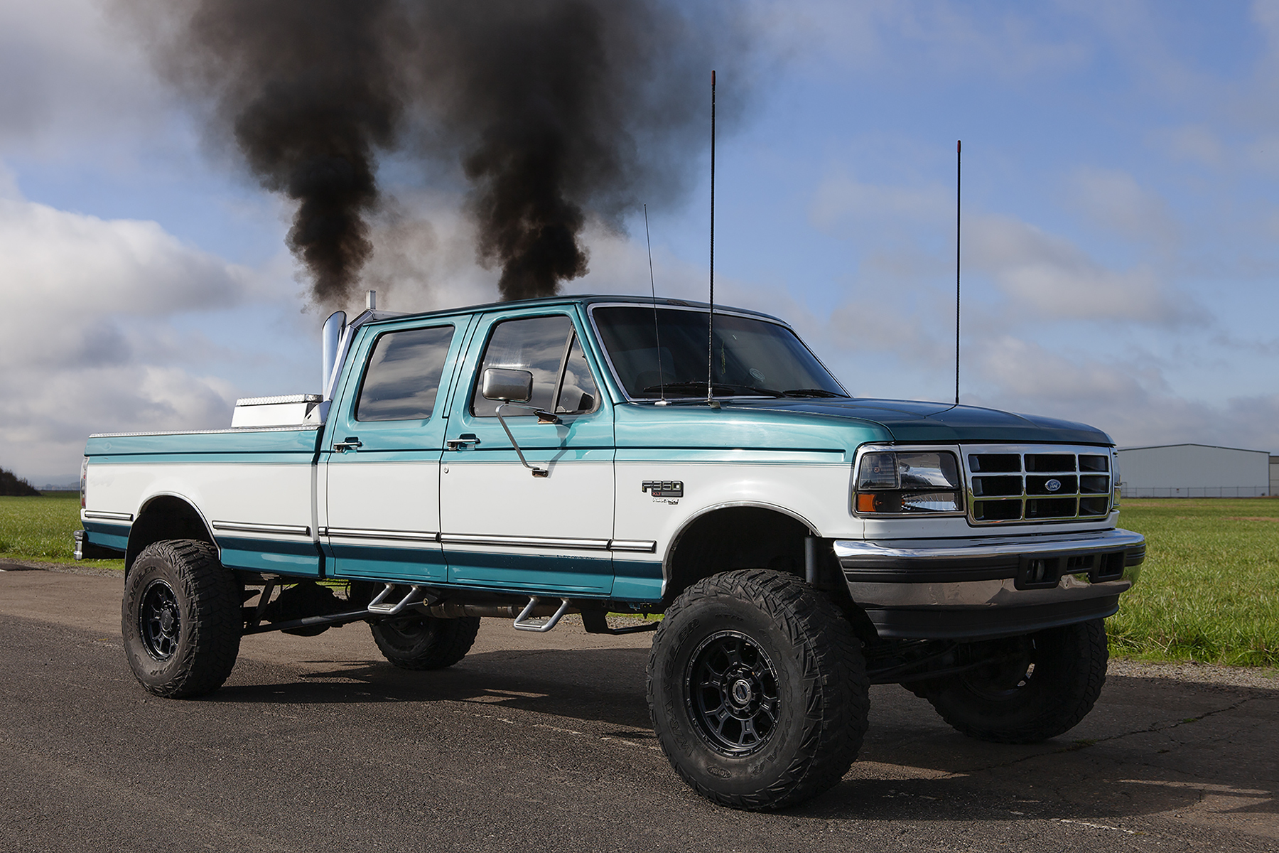 Photograph of a blue and white pickup truck driving on a road. The view is from the side of the truck, asphalt in the foreground, grass and partly cloudy sky in the background. Two dark black plumes of smoke rise from the exhaust pipes on the back of the cab of the truck.