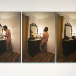 Three large scale framed color photographs hang on a white wall. The images on each photo are sequential, and take place in the same setting. The photo on the left depicts a naked man, holding a bible, standing in front of a dresser with a mirror on it. He is pointing at himself in the mirror. The center photo shows the man with his head thrown back and his mirror image is yelling. The photo on the right shows the same man bent with his hands down and his head resting on the bible which is on the dresser.