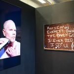 """Installation view of a corner a gallery; the walls are black and meet at the center of the image. On the left is a video monitor with an image of a man with a clean shaven head who is shaving his chin with an electric razor. On the left wall is a photo of a black board with the words """"Katie May Everett Daniel the only good I ever did"""" written on it in white block letters."""