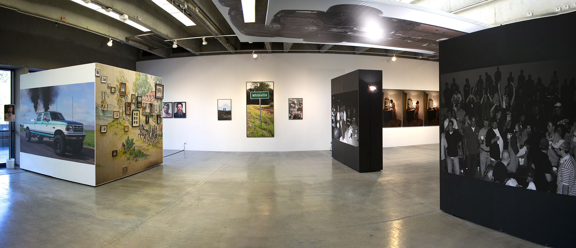 """Panorama view of gallery showing an installation of large scale photographs. On the left is a freestanding wall with a photo of a pick up truck and a wall of smaller framed photos. On the right are two freestanding walls painted black and that have black and white photos of people on them. In the background is a white wall with several photos hanging on it. At the center of the back wall is a lifesize photo of a sign that says """"Whiteville."""" Hanging horizontally on the ceiling at center right is panel with a photo of a car's underside on it."""