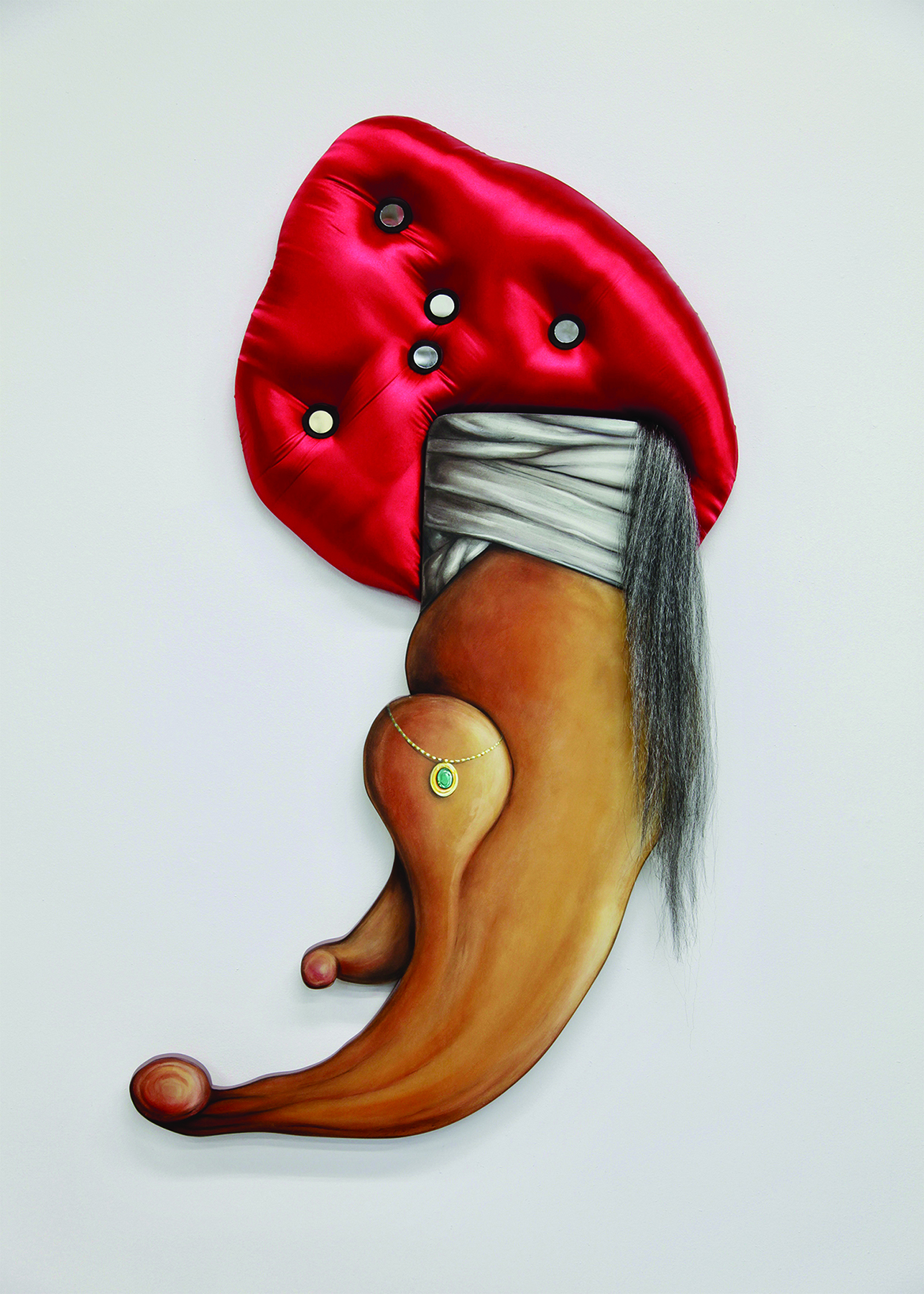 Mixed media sculpture hangs on a white gallery wall. The lower half of the artwork is painted wood and depicts a jeweled necklace and white wrapped fabric. The upper part of the piece is a padded turban like shape made of shiny red fabric, with white buttons imbedded in it. A tail like drape of artificial grey hair is draped on the right side of the object.