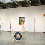 : Installation view of gallery shows five large scale mixed media sculptures hanging on a white wall in the background and one mixed media sculpture on the floor in the foreground. The artworks lean on the wall and/or sit on the floor and are abstract and multicolored.