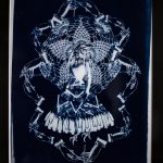 A cyanotype print in a black frame. A central female figure with a birds head, wears a skirt of feathers, and has bird claws for feet. A lace doilly is behind her, like a halo. Surrounding the iconic form is an undulating border or hands with knitting needles. The image is printed in tones of indigo and white, with a very dark blue in the background.
