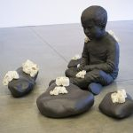 Sculptural installation made of stoneware and porcelain, placed on a concrete gallery floor, with a white gallery wall in the background. The installation features a sculpture of a lifelike depiction of a small boy sitting crosslegged on the floor. There are four large stones arranged around him. The boy and stones are monochromed in a dark brown color. On top of the stones and the boy are sculptures of white barnacles, also realistically rendered. The boy is looking at the stones.