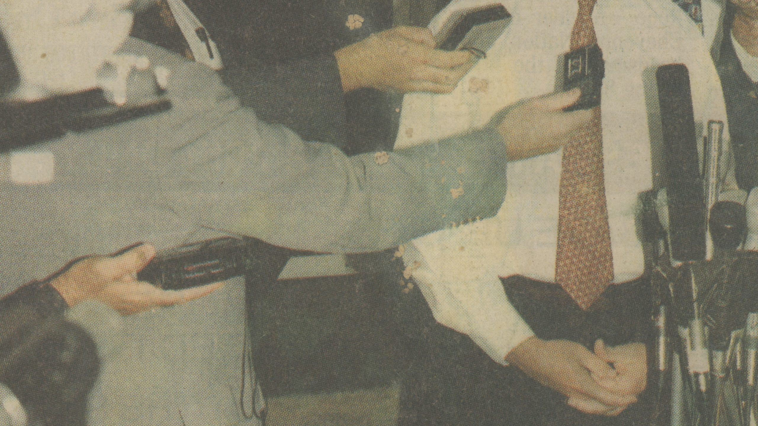 A video still of Untitled (Saturday, October 16, 1993) shows a weathered newspaper clipping of a figure dressed in a white shirt with red tie standing before microphones. Arms reach out from the left side of the shot with tape recorders and additional microphones preparing to record the speaker's voice.