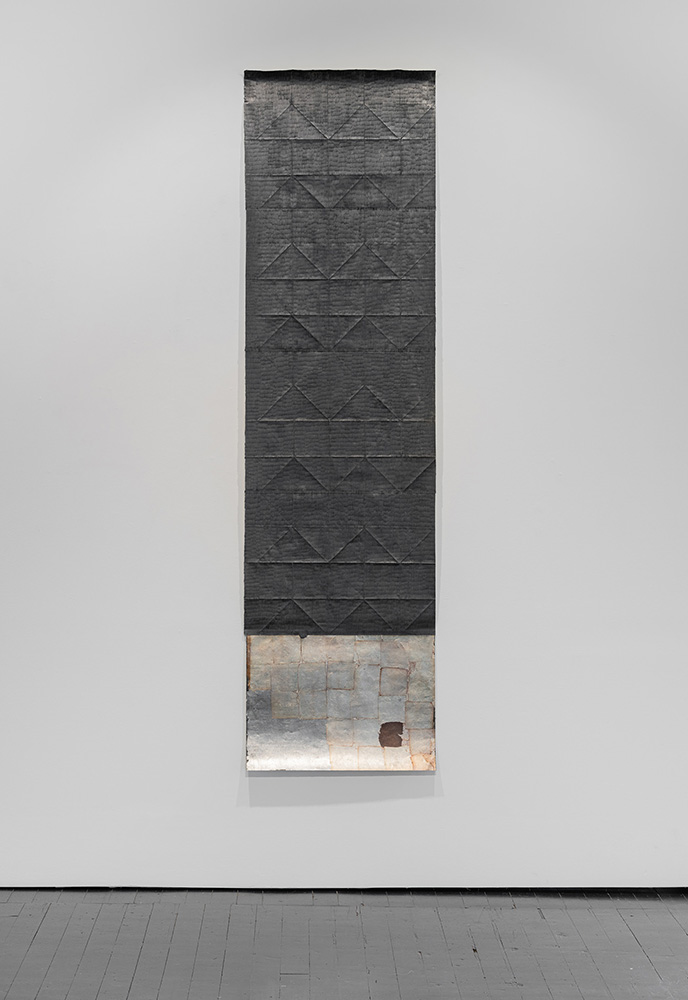 Jenene Nagy artork of vertical dark gray paper with a triangular texture hanging in a gallery