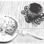A black and white drawing of a plate of eggs on toast with a dark mug full of tea. A metallic fork rests partially on the edge of the plate and angles downward to touch the wood-grain table.