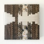 """""""A multi-colored and textural weaving of fabric and mixed medias on a wooden panel board with alternating strips of fabric layered on top of each other. """""""