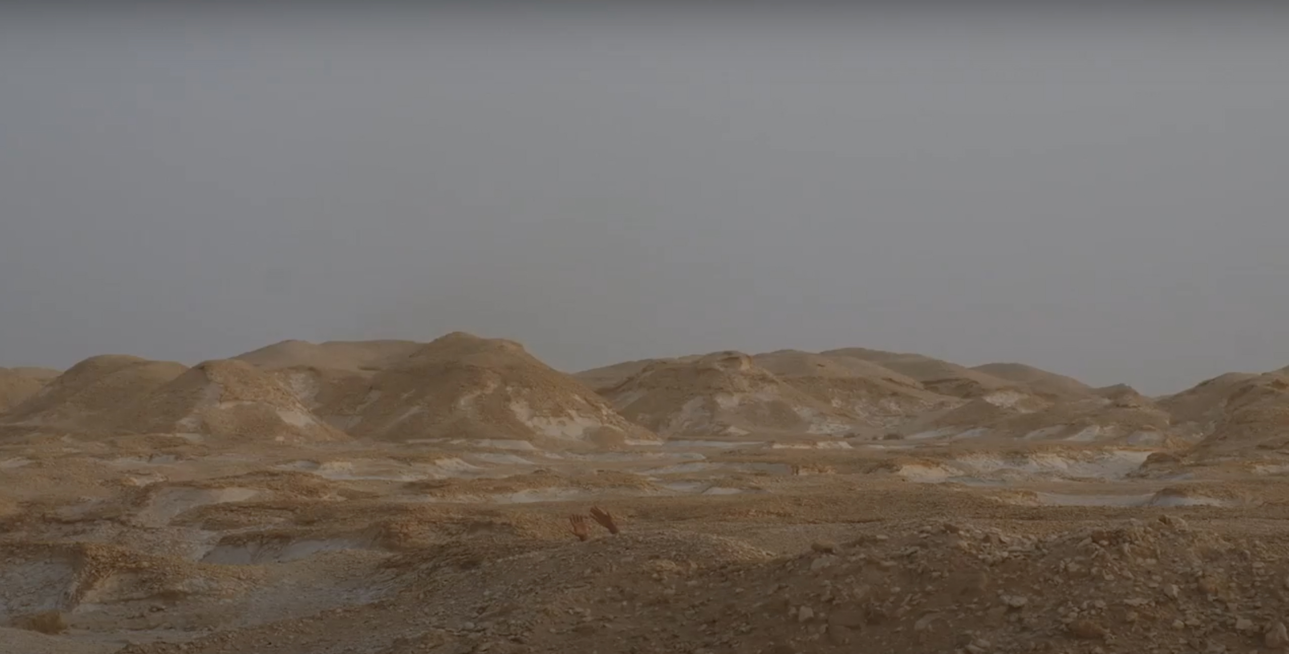 video still of a desert like landscape with two hands raised behind a small hill