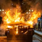 Image shows a garbage dumpster, which is on fire, blocking the middle of a street in downtown Portland.