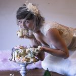 Person in a wedding dress eating cake with their hands.