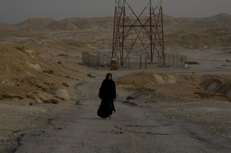 photograph of a figure walking in a desert-like landscape