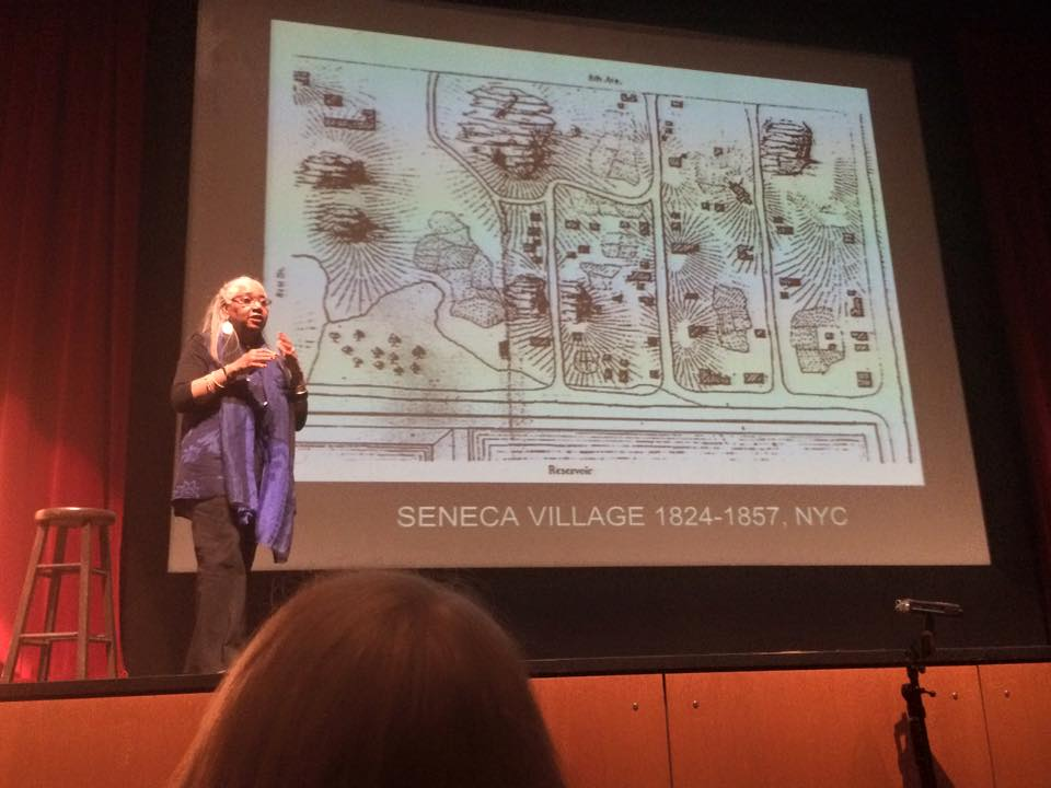 Scholar speaking in front of an audience, with a drawing of the Seneca Village projected on the screen in the background.