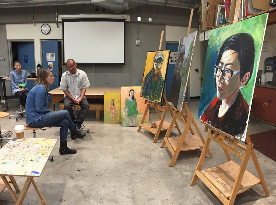 Artist and two students sitting and looking at a group of paintings on easels.
