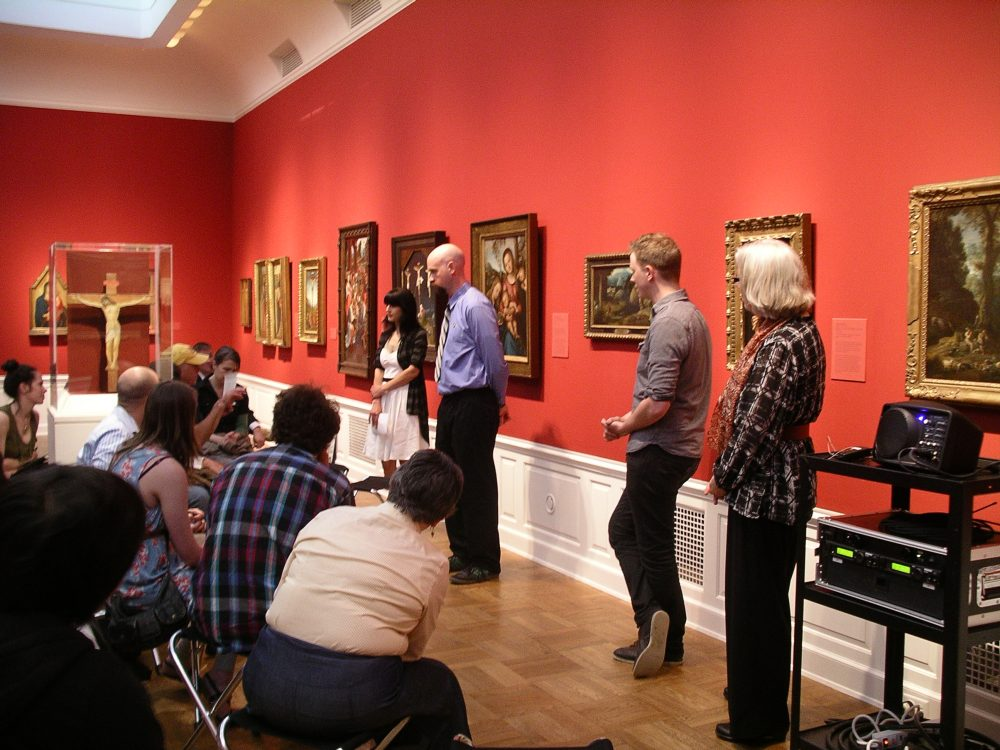 Students standing in front of paintings with an audience sitting on chairs in front of them.