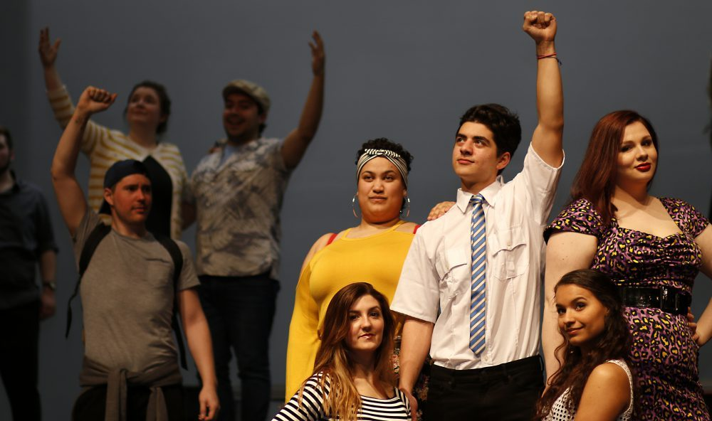 Actors performing on stage with arms raised in fists.