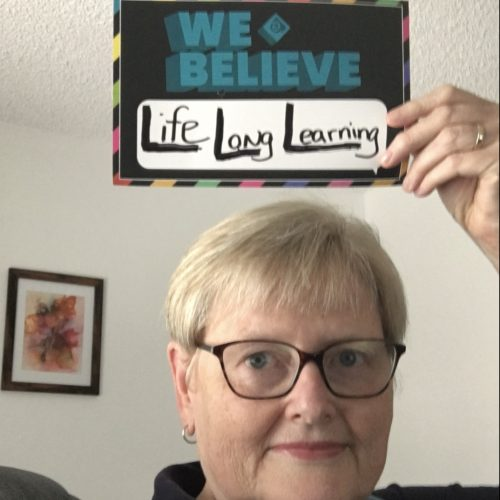 Woman holding sign that says we believe in life long learning