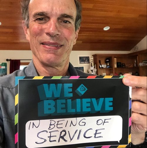 Man holding sign that says we believe in being of service