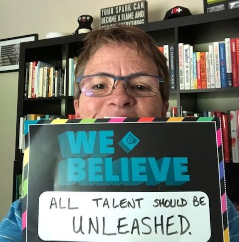 Woman holding sign that says we believe all talent should be unleashed