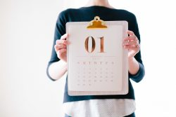 image of person holding a clipboard with a calendar on it