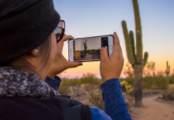image of a woman recording video of desert with iPhone