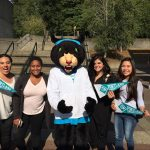 four female students pose for a picture with school mascot, poppy the panther
