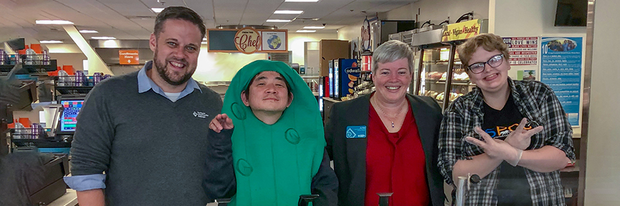 Students, staff, and student in a pickle costume pose near cafeteria