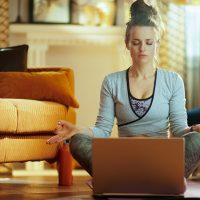 relaxed healthy sports woman in fitness clothes at modern home meditating using online streaming yoga site in laptop.
