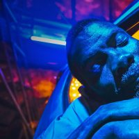Photo of a sleeping man under bright blue lights, taken from one of the films