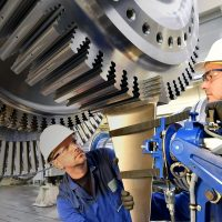 Workers assembling and constructing gas turbines in a modern industrial factory