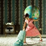 Figurine of a woman vacuuming and holding a globe on her back. The TV in the background shows an atomic bomb exploding.