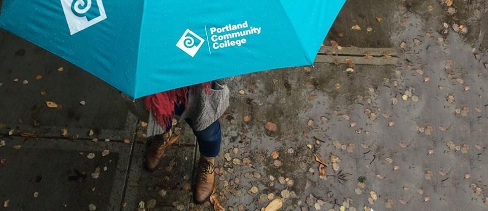 PCC branded umbrella outside in the rain