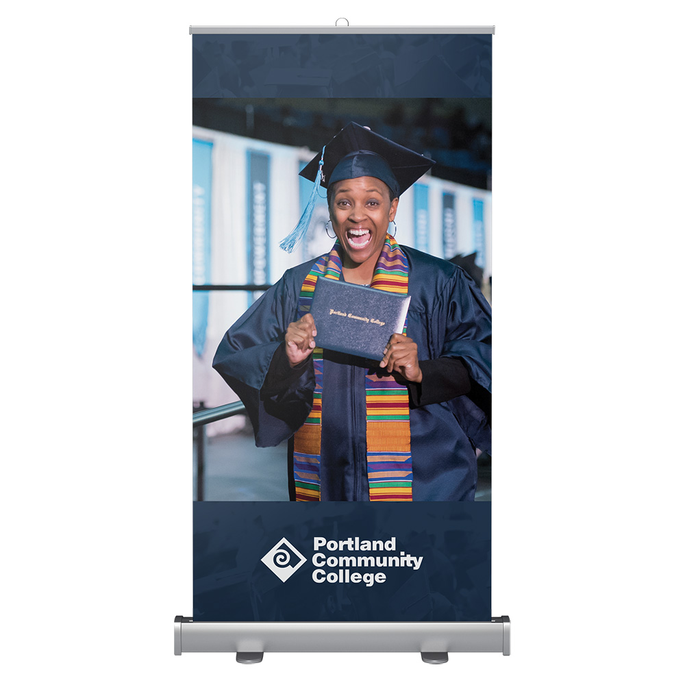 Wide banner stand with student at graduation holding their diploma